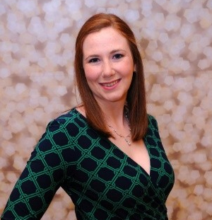 Photo of Flourishing Professional co-creator Melissa Skolnick a red -haired woman in a green and blue dress